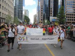 OutSport Toronto directors carrying the banner in front of the sport and rec contingent in the parade.